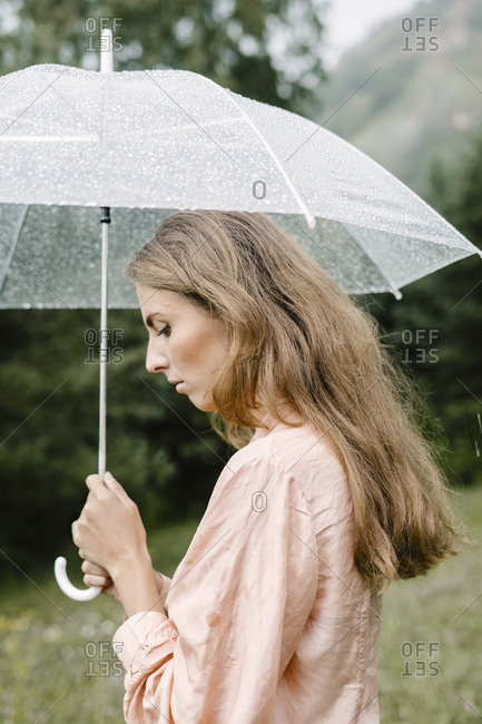 Profile view of a blonde woman holding clear umbrella from behind