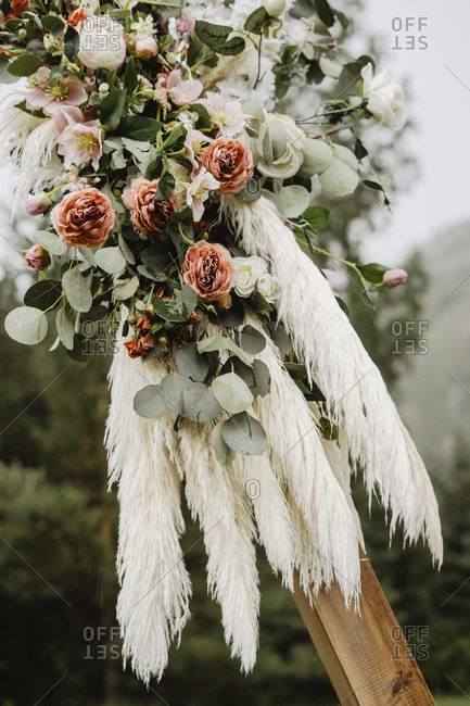 Floral arrangement with feathers at a country wedding ceremony