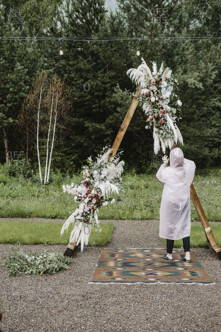Person fixing floral arrangement on an alter at a wedding ceremony in the rain