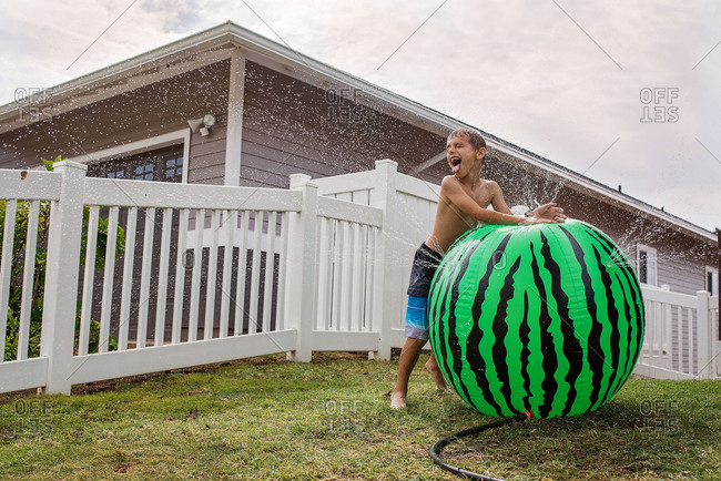 Boy playing with large inflatable sprinkler water toy in the yard