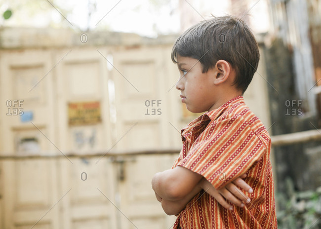 Portrait of a boy with crossed arms wearing traditional Indian clothing on the streets in India