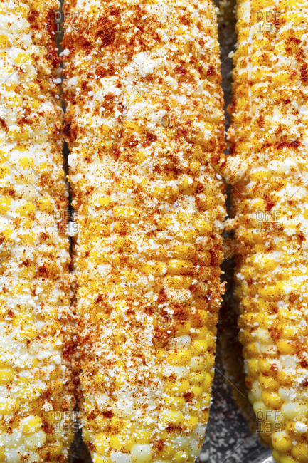 Close up of boiled corncob with mayonnaise, sour cream with cojita cheese and smoked chili powder