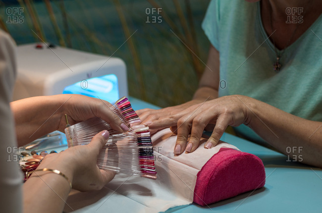 Center of manicure and pedicure where there is a lady painting the nails of the hands and feet