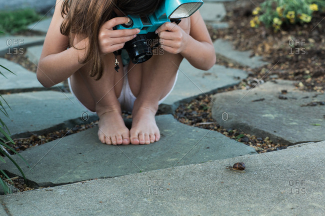 Girl photographing a snail with a vintage camera
