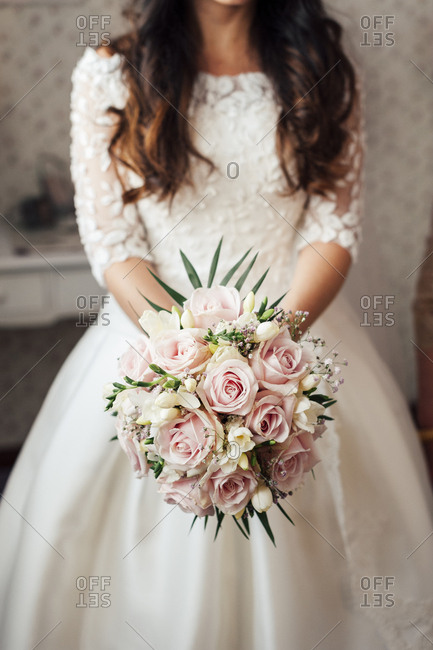 Crop unrecognizable bride with beautiful bunch of pink and white flowers.