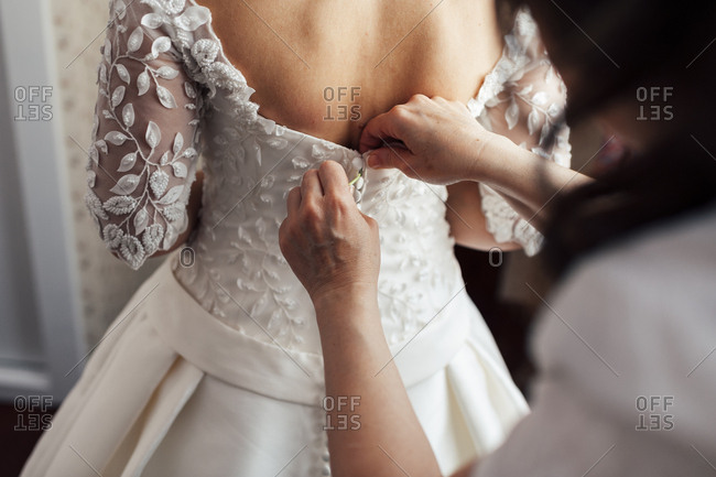 Hand helping to unrecognizable bride to button white dress.