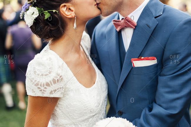 Crop happy newlywed couple kissing on the wedding event.