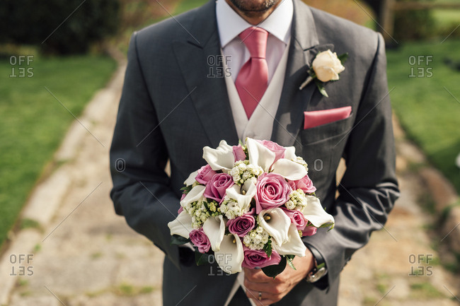 Crop handsome man in gray suit standing with bunch of pink and white flowers.
