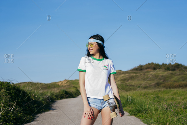 Stylish teen girl with long board in summertime