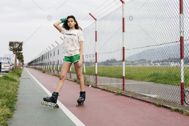 Casual teen girl in shorts and roller skates standing on lane of sports ground looking at camera.