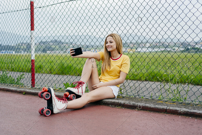 Teen girl wearing roller skates and showing two fingers at camera of smartphone taking selfie on street.