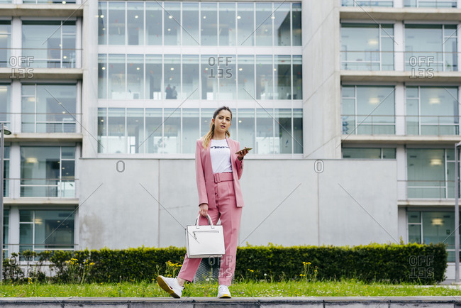 Young stylish model in pink suit holding smartphone and handbag standing on street looking at camera.