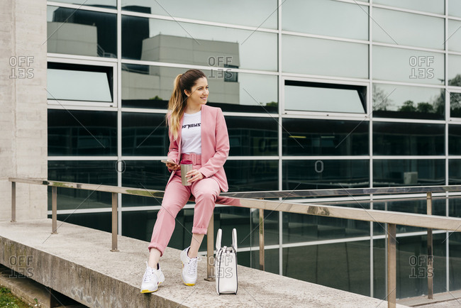 Stylish girl in pink suit with sneakers sitting on fence holding coffee and smartphone smiling away.