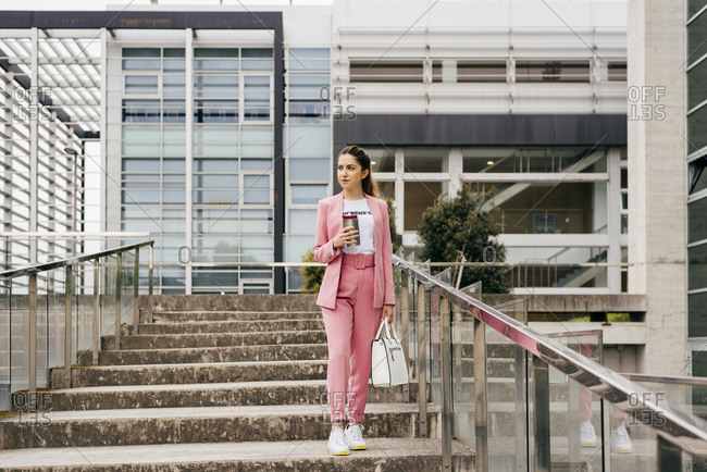Young pretty woman wearing pink suit with white sneakers walking down stairs with coffee cup on street.