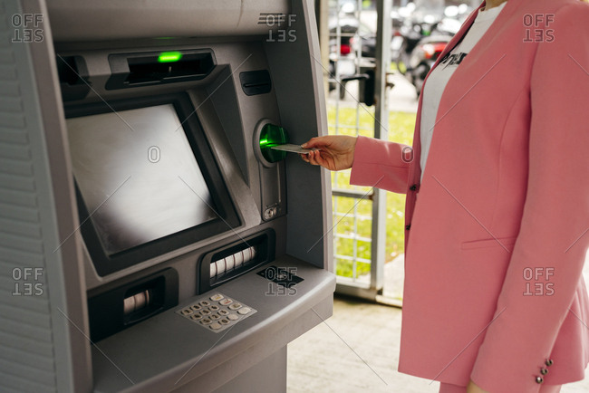 Faceless shot of woman in suit inserting credit card into ATM machine standing on street.