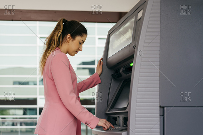 Crop woman using ATM machine