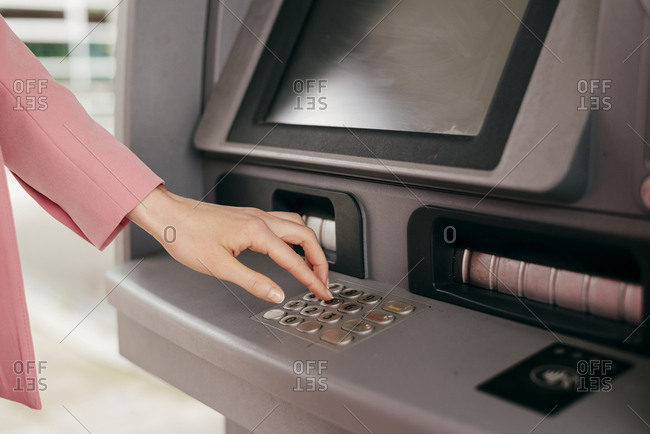 Crop shot of woman in pink entering PIN code for in ATM machine operating with credit card.