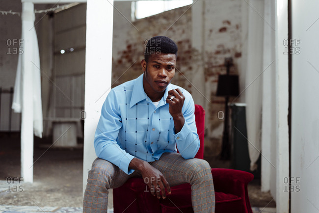 Elegant African-American man sitting on arm pad