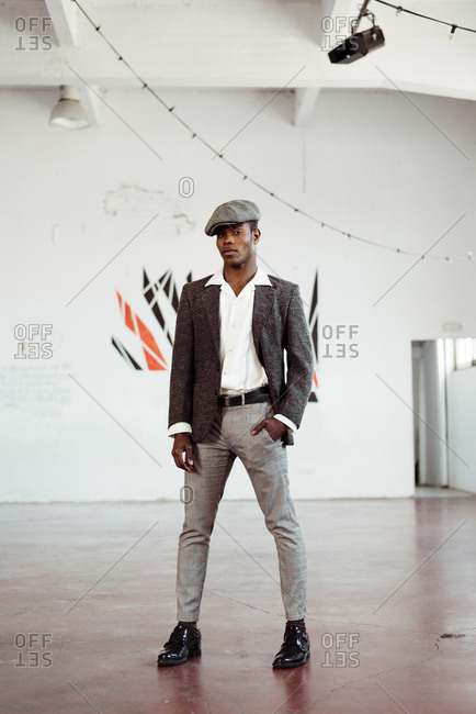 Positive black man in retro outfit looking at camera while standing in light broad room