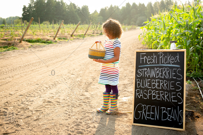 Girl standing by chalkboard sign at a U-pick farm