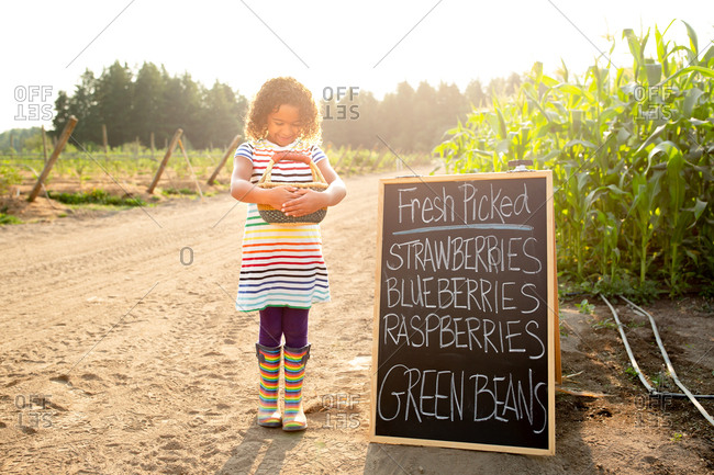 Girl standing by chalkboard sign at a U-pick farm holding basket