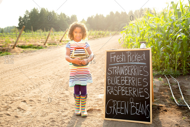 Happy girl standing by chalkboard sign at a U-pick farm holding basket