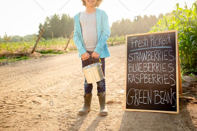 Boy standing by chalkboard sign at a U-pick farm