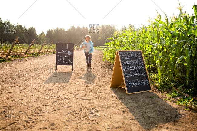 Boy walking by chalkboard sign at a U-pick farm