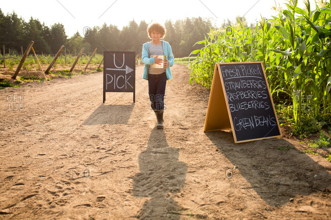 Young boy walking by chalkboard sign at a U-pick farm
