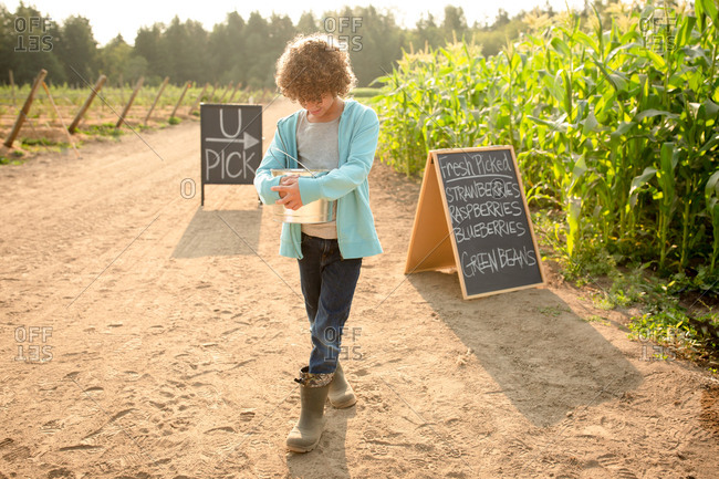 Young boy with bucket by chalkboard sign at a U-pick farm