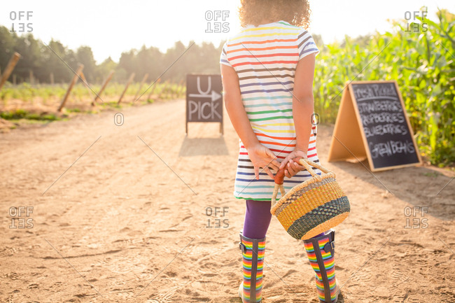 Rear view of girl standing by chalkboard sign at a U-pick farm