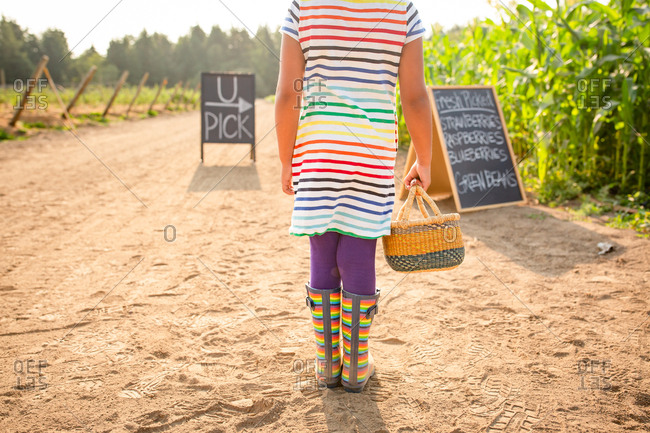 Back view of girl standing by chalkboard sign at a U-pick farm