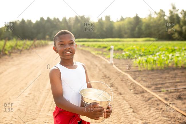 African American boy holding bucket on a farm
