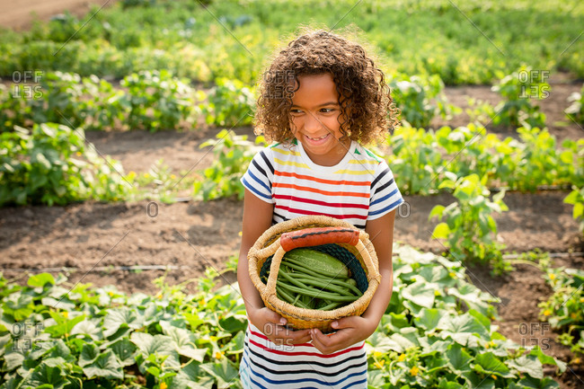 Happy girl holding basket with vegetables on a farm