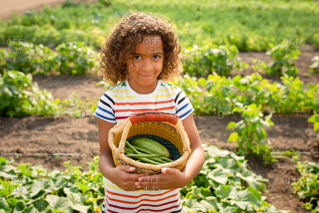 Little girl holding basket with vegetables on a farm