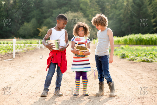 Three siblings holding containers of fresh picked vegetables on a U-pick farm