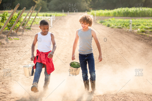 Two brothers walking on dusty path on a farm