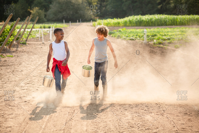 Brothers walking on dusty path on a farm