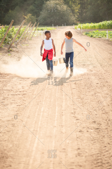 Two brothers walking on dusty farm path