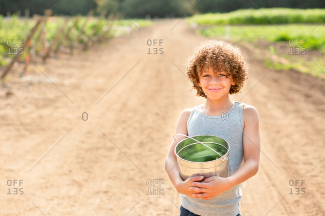 Boy holding bucket of vegetables on a farm