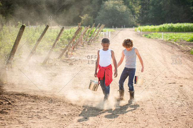 Two young boys walking on dusty farm path