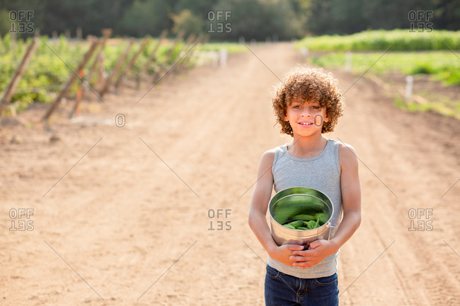Young boy with curly hair holding bucket of vegetables on a farm