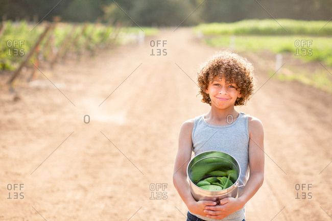 Happy boy holding bucket of vegetables on a farm