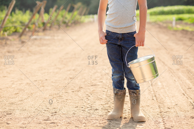 Young boy holding bucket on a farm