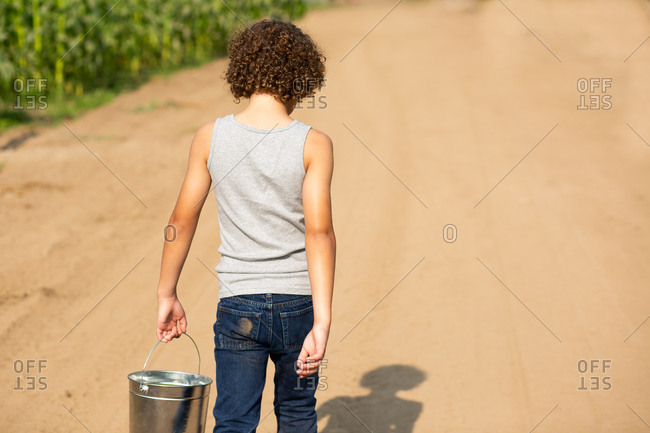 Young boy with curly hair walking with bucket of vegetables on a farm