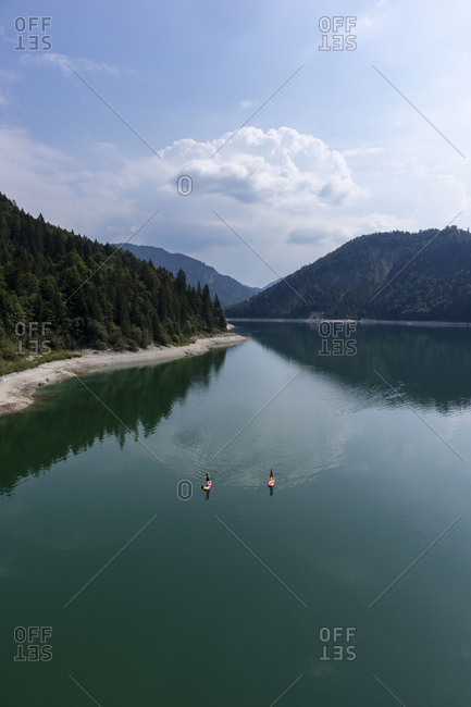 Two people stand up paddle boarding on wilderness lake