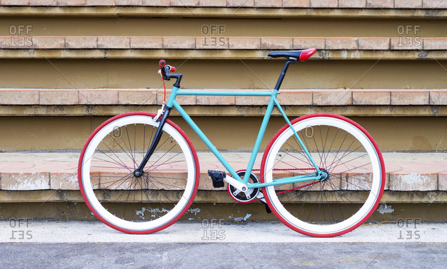 Minimalist colored single speed bicycle against stair