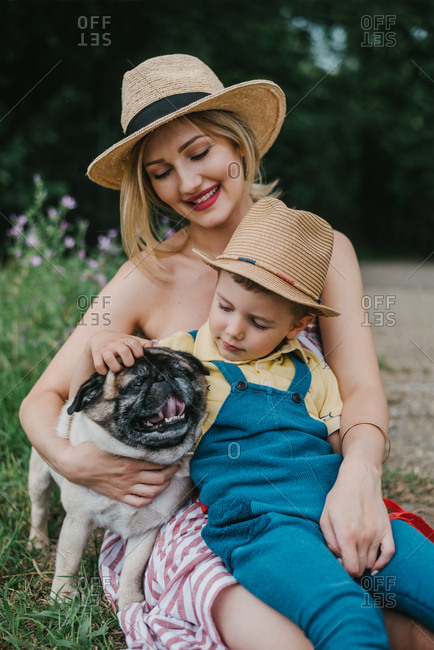 Mother and son with their dog sitting in a grass and enjoying