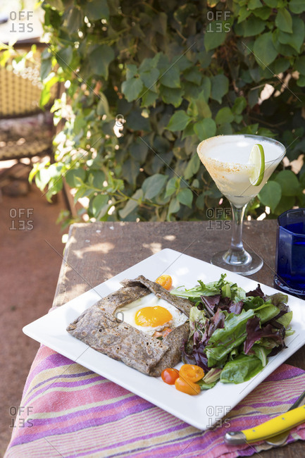 Crepe with sunny side up egg served with side salad and drink for brunch