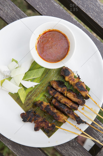 Satay served on a banana leaf with sauce and a side of fresh cucumber